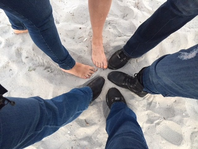 FBGz members putting their feet together in the sand