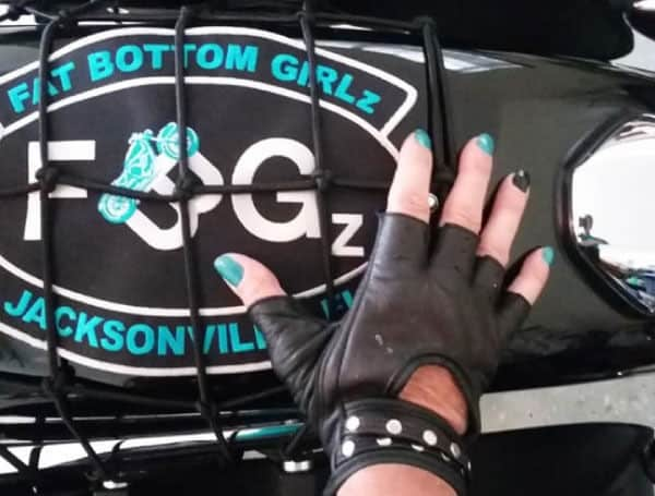 A woman in biker gloved putting her hand against a FBGz logo