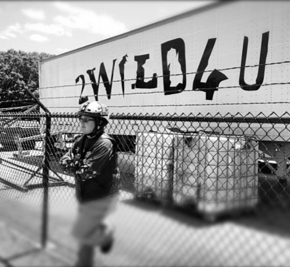 A FBGz member next to a sign that says 2 Wild 4 U