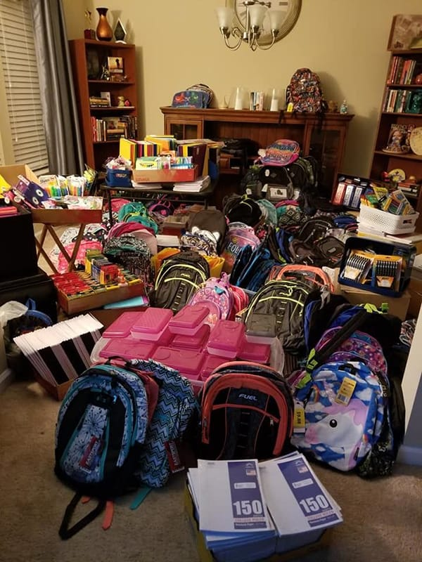 A photo of a bunch of new backpacks and school supplies