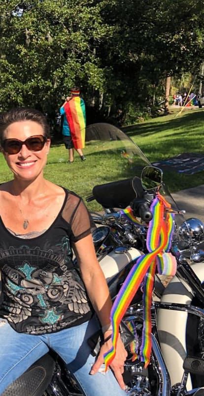 A FBGz member with a motorcycle with rainbow ribbons